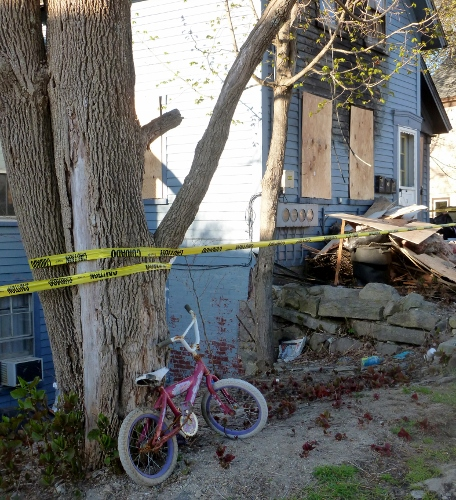 child's bicycle leans against a tree after a fire